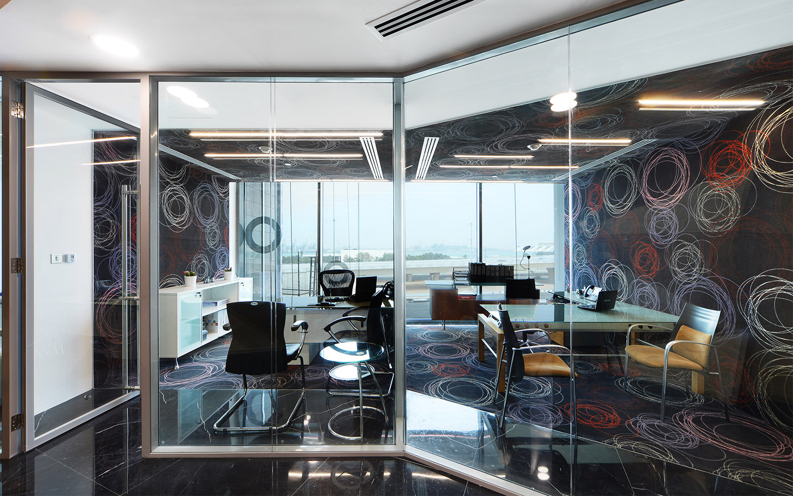 Wall-to-wall carpet for office design by ege, where colourful scribble-like patterns meet a stark black tile surface for a bold effect