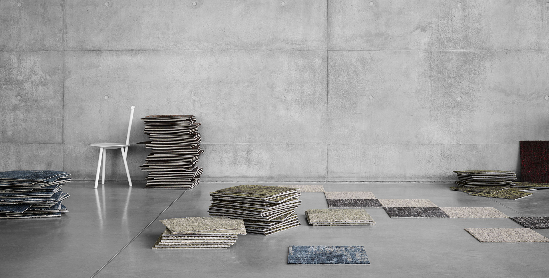 pile of carpet tiles in different colours laying out on the floor and in a pile against a white chair