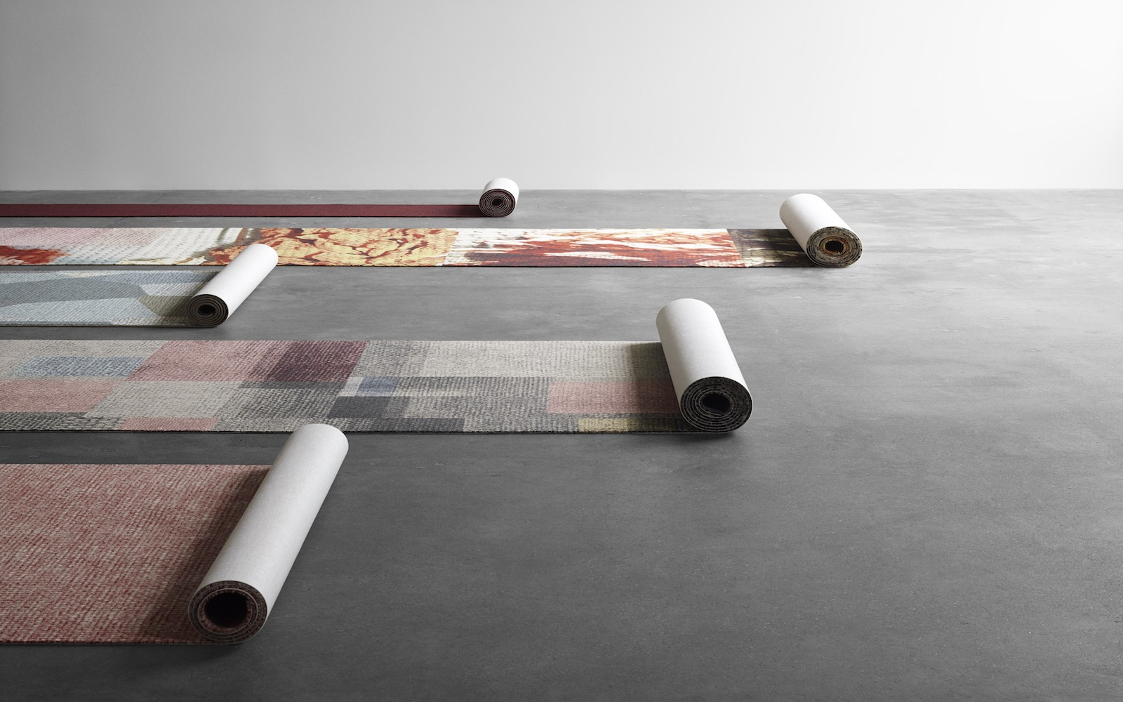 rolls of wall-to-wall carpet in different colours and patterns showcasing ege's wide variety of carpet choices