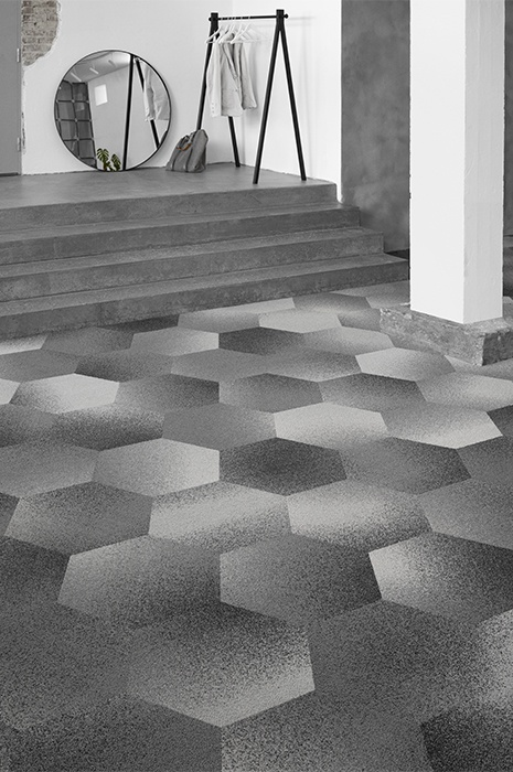 Custom designed hexagon shaped carpet tiles leading up a short staircase to a round mirror