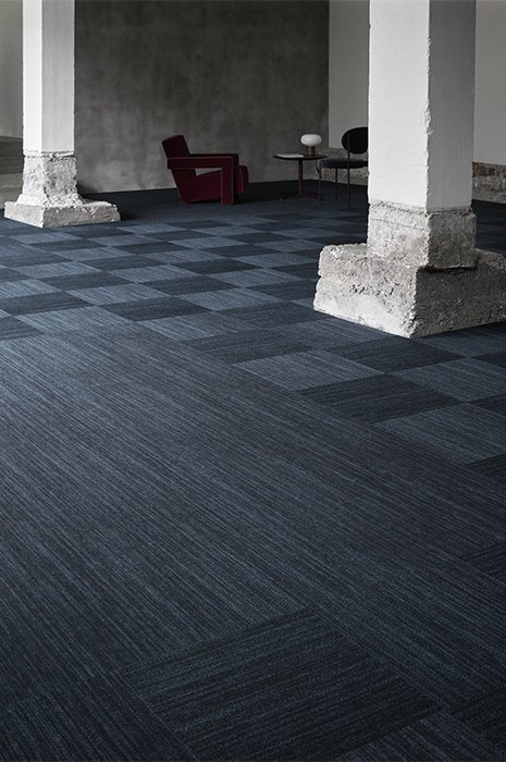 Vast room with big concrete pillars and blue toned carpet tiles for flooring