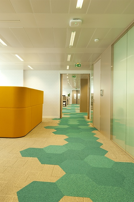 Hexagon-shaped carpet tiles by ege in different shades of green and yellow used for wayfinding in an office