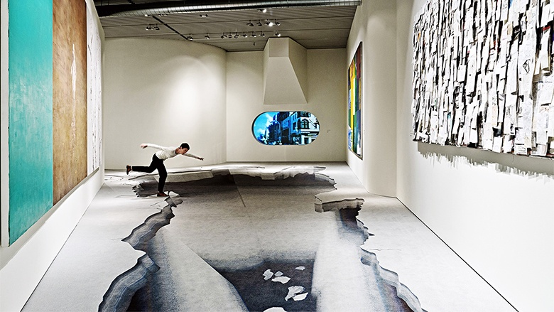 A custom wall-to-wall carpet by ege creating the illusion of a large body of water. A women is pretending to jump into it.